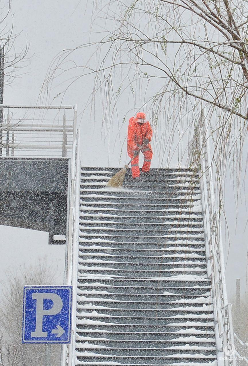 在山西省大同市永和路街区人行天桥上,一位环卫工人正在冒雪清扫台阶积雪。 孙一越