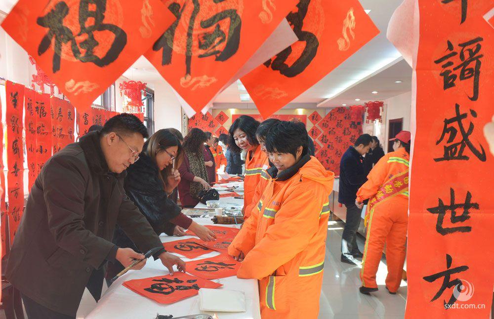 大同市文艺志愿者们走进环卫工当中,挥毫泼墨写春联,送去新春的祝福   刘刚摄